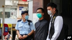 FILE - Simon Leung Kam-wai, center, a committee member of the Hong Kong Alliance in Support of Patriotic Democratic Movements of China, is escorted by police during an investigation of the June 4th Museum in Hong Kong.
