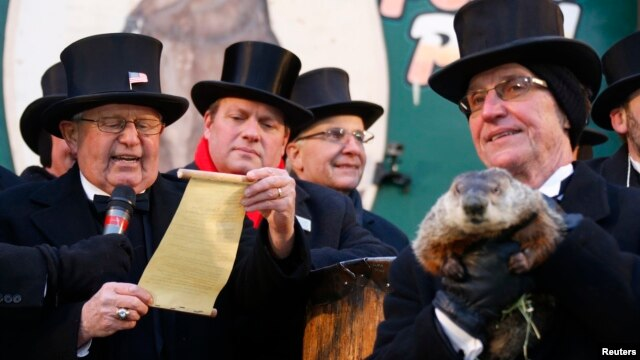 Groundhog co-handler Ron Ploucha (R) holds Punxsutawney Phil as the Groundhog Club's Bob Roberts (L) reads the famous groundhog's annual weather prediction on Gobbler's Knob in Punxsutawney, Pennsylvania, on the 127th Groundhog Day, Feb. 2, 2013.