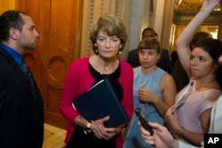FILE - In this July 28, 2017, file photo, Sen. Lisa Murkowski, R-Alaska, passes reporters as she leaves the Senate chamber on Capitol Hill in Washington. Conservatives across the country warned that the GOP-led Congress could not abandon its pledge to repeal and replace Obamacare without suffering losses in the next election.