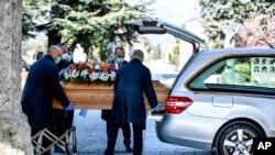 Les pompes funèbres transportent un cercueil d'un corbillard au cimetière de Bergame, dans le nord de l'Italie, le lundi 16 mars 2020. Bergame est l'une des villes les plus touchées par la nouvelle épidémie de coronavirus. (Claudio Furlan / LaPresse via AP)