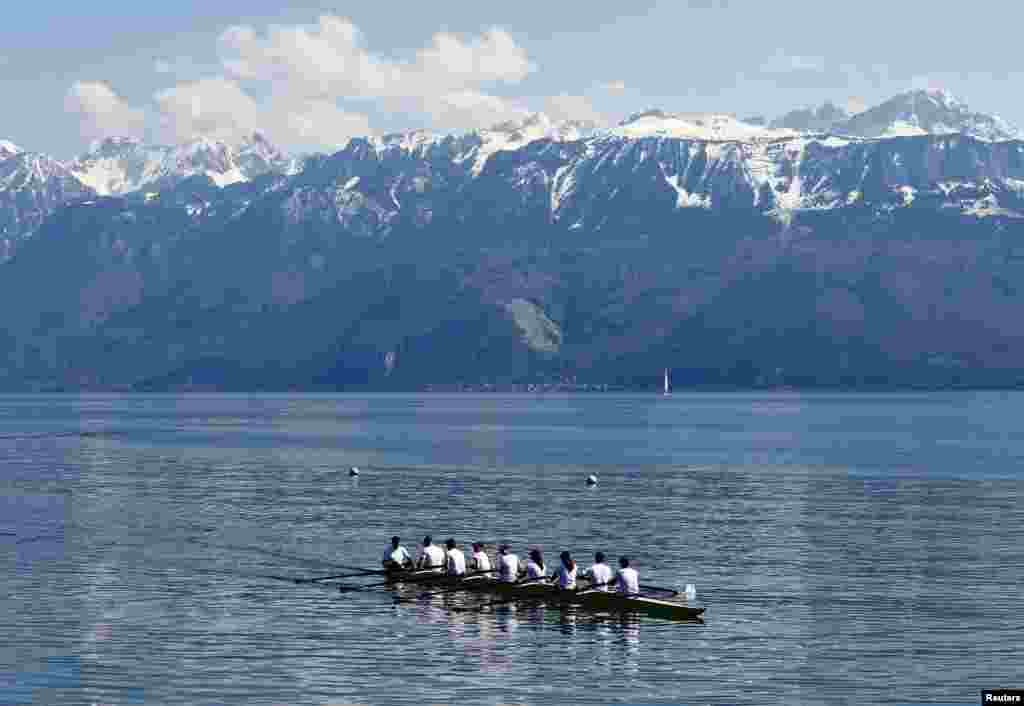 The Olympic flame is transported by a rowing boat of the Lausanne-Sport on Lake Leman before arriving at the Olympic Museum in Lausanne, Switzerland.