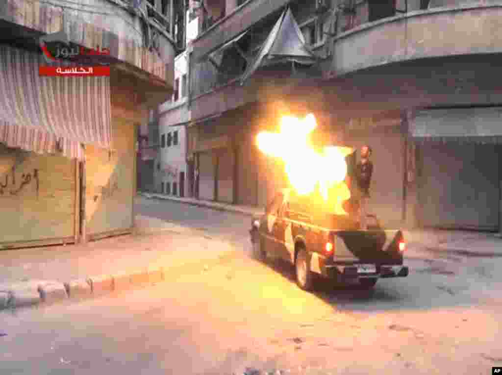 In this image taken from video from the Shaam News Network, fighters from the Free Syrian Army target regime forces in Aleppo, Syria, July 22, 2013.