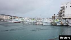 这种由共同社拍摄的照片显示,渔船在台风浣熊袭来之前用缆索固定在冲绳南部那霸的泊港。(2014年7月7日)