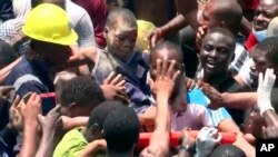 In this image taken from video, people help a child after he was rescued from the scene of a building collapse in Lagos, Nigeria, March 13, 2019.