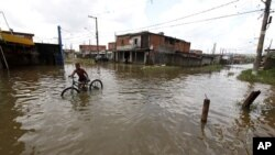 A boy pushes his bicycle in a flooded street after heavy rains at Jardim Pantanal neighborhood in Sao Paulo, 15 Jan 2011