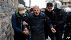 Plainclothes police detain a man in Istanbul, one of more than 200 people who were protesting peacefully against curfews and operations in mainly Kurdish cities and towns in southeastern Turkey, Jan. 3, 2016.