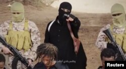 FILE - An Islamic State militant holds a gun while standing behind what are said to be Ethiopian Christians in Wilayat Fazzan, in this still image from an undated video made available on a social media website on April 19, 2015.