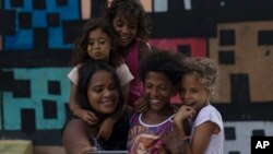 Artist Mariluce Maria de Souza takes a selfie with several children from her workshop, in front of one of her murals in the Alemao slum of Rio de Janeiro, Brazil, March 7, 2017.