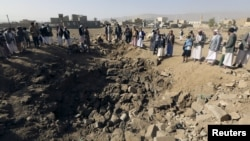 People gather around a crater cause by an airstrike in Amran province, northwest of Yemen's capital, Sana'a, April 12, 2015.