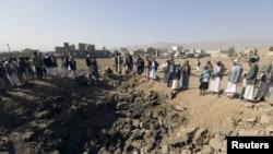 一些也门人聚集在沙特空袭造成的一个大坑旁边