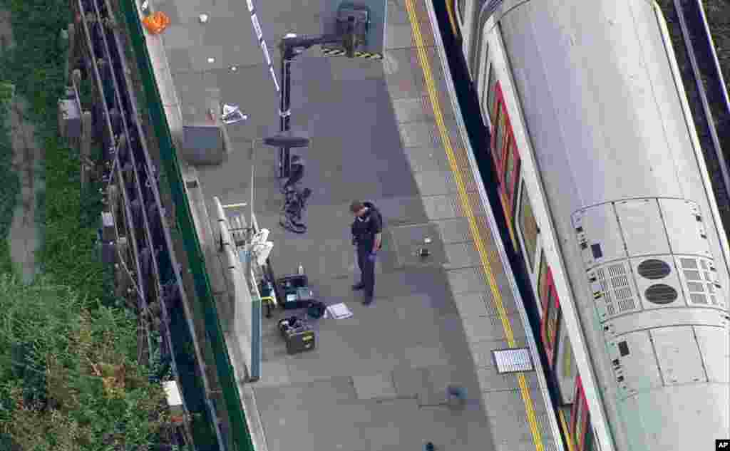 In this aerial image made from video, a police officer works at the Parsons Green Underground Station after an explosion in London Friday, Sept. 15, 2017.