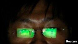 一位不愿意透露姓名的黑客正在位于台北的办公室中使用电脑。(资料照片)