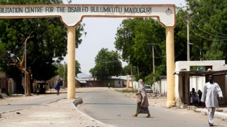 A woman crosses a deserted road in Bulumkutu, after the military declared a 24-hour curfew over large parts of Maiduguri in Borno State May 19, 2013.