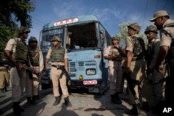 Indian security personnel stand guard near paramilitary soldiers' bus that was damaged in an ambush by suspected rebels in Pampore, on the outskirts of Srinagar, Indian-controlled Kashmir, June 25, 2016.