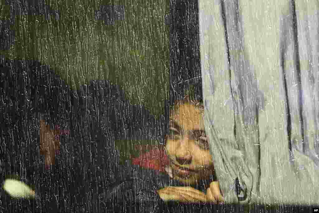 A girl looks out from a window of a bus which will transport migrants and refugees to a camp, after they were registered by authorities in Brezice, Slovenia.