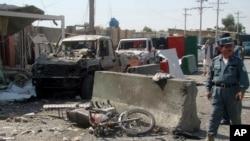 Seorang polisi tengah memeriksa lokasi serangan bom bunuh diri di Lashkar Gah, Ibukota Provinsi Helmand (8/10).