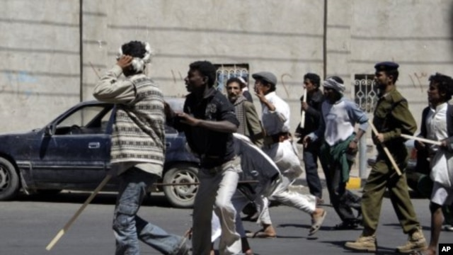 Government backers chase anti-government protesters during clashes in Sanaa, February 14, 2011