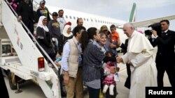Le pape François accueille un groupe de réfugiés syriens à l'aéroport de Ciampino à Rome, le 16 avril 2016.