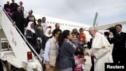 Paus Fransiskus menyambut sekelompok pengungsi Suriah setelah mendarat di bandar udara Ciampino di Roma setelah mengunjungi kamp pengungsi Moria di pulau Lesbos, Yunani (16/4). (Reuters/Filippo Monteforte)