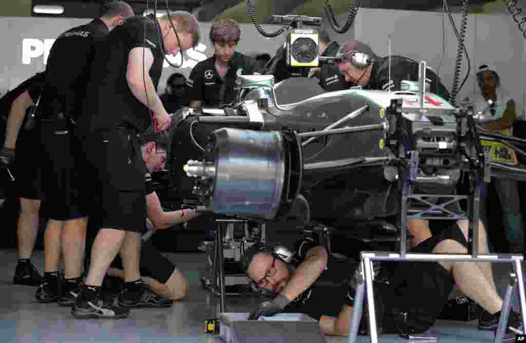 Mercedes mechanics fix British driver Lewis Hamilton's car at the team's garage after its engine failure during the first practice session for the Malaysian Formula One Grand Prix at Sepang International Circuit in Sepang, Malaysia.