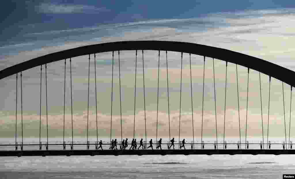 A group of joggers run across the Humber Bay Arch Bridge during extreme cold temperatures in Toronto, Canada.