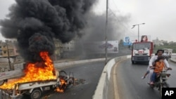 A family on a motorbike rides past a burning vehicle set ablaze by protesters in Karachi , July 14, 2011