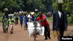 FILE - A Malawian man transports food aid distributed by the United Nations World Food Progamme (WFP) through maize fields in Mzumazi village near the capital Lilongwe, Feb. 3, 2016.