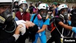 Voluntarios de la Cruz Verde atienen a una mujer herida durante la marcha contra el hambre en Caracas.