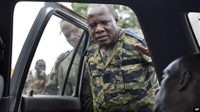 Soldiers loyal to Alassane Ouattara look at the body of a civilian who they say died as they tried to transport him for medical help at their operating base, after he was allegedly shot by militiamen loyal to Laurent Gbagbo, in Abidjan, Ivory Coast, April