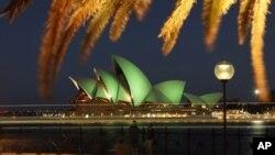 Wisatawan mengabadikan suasana di sekitar Sydney Opera House yang berhiaskan cahaya hijau dalam perayaan Hari Santo Patrick di Sydney (17/3).