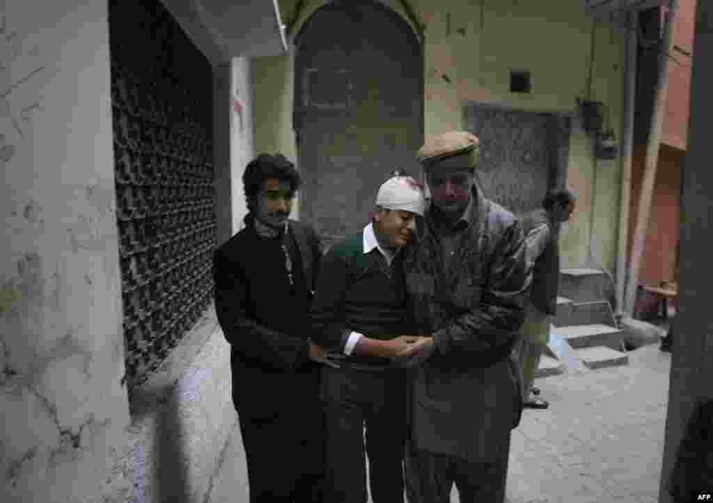 The uncle and cousin of injured student Mohammad Baqair, center, comfort him as he mourns the death of his mother who was a teacher at the school in Peshawar, Pakistan. Taliban gunmen stormed a military-run school in the northwestern city, killing more than 100, officials said
