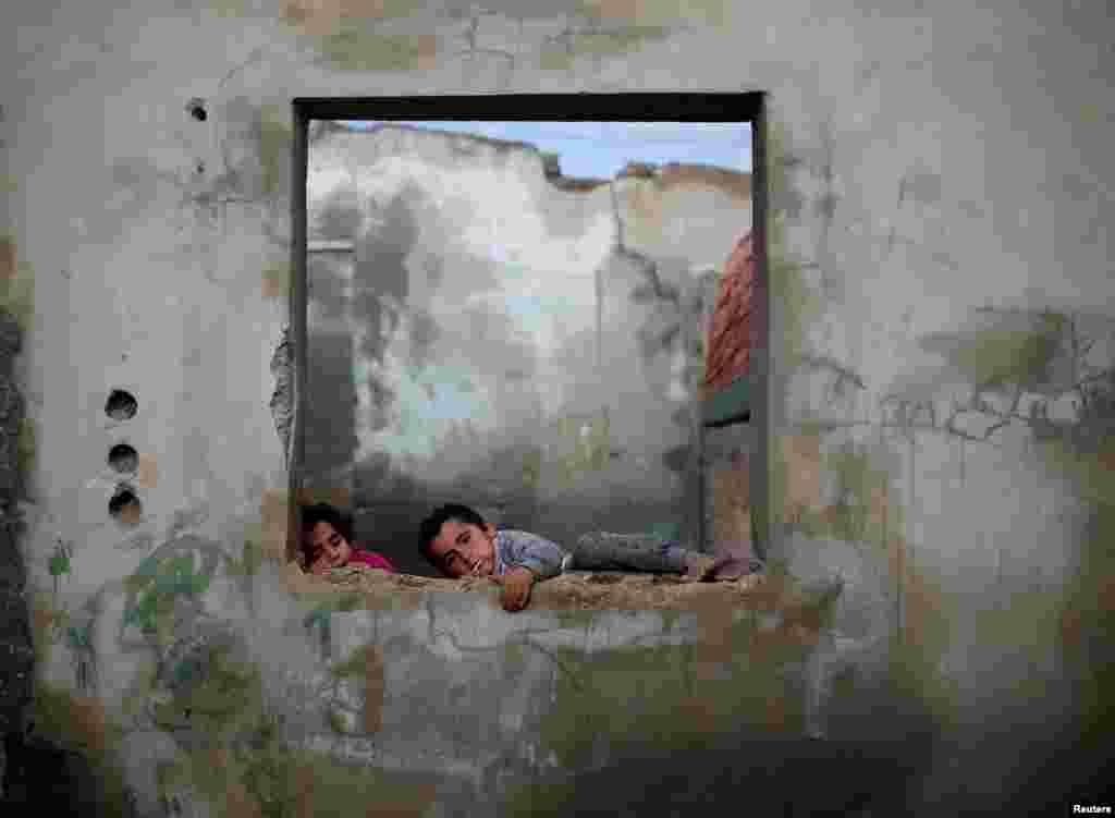 Gazze'de Al-Shati mülteci kampında yıkık dökük evlerinin içinde oynayan çocukların fotoğrafı çekilmiş.