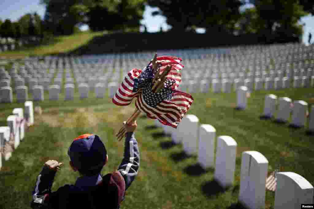 Một hướng đạo sinh Mỹ cắm quốc kỳ Mỹ tại các ngôi mộ trong nghĩa trang Quốc gia Cypress Hills, ở Brooklyn, New York, 23/5/15