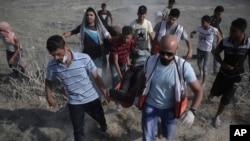 7月21日巴勒斯坦人在以色列跟加沙交界处跟以色列军人发生冲突。图中巴勒斯坦医护人员和抗议者疏散一名冲突中受伤的男子。