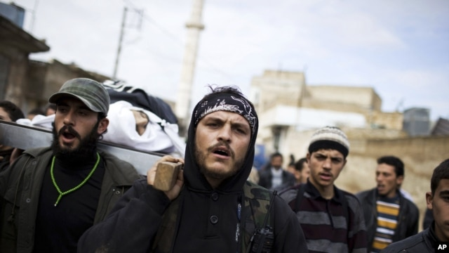 Free Syrian Army fighters carry the body of a comrade killed by the Syrian Army in Azaz, Syria, Dec. 13, 2012