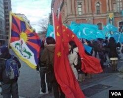 支持和抗议中国政府的人并肩扛旗站在白宫附近