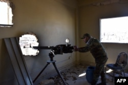 A fighter from the Syrian pro-government forces mans a gun inside damaged houses as they approach the Baeedin district in eastern Aleppo, near Masaken Hanano, November 23, 2016.