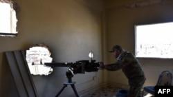 叙利亚亲政府部队战士在被摧毁的房屋里面手把机枪。(2016年11月23日 资料照片)