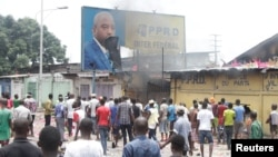 FILE - Congolese opposition supporters chant slogans as they deface a billboard featuring President Joseph Kabila during a march to press him to step down, in the Democratic Republic of Congo's capital Kinshasa, Sept. 19, 2016.