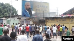 FILE - Congolese opposition supporters chant slogans as they destroy a billboard display of President Joseph Kabila, during a march to press the president to step down, in the Democratic Republic of Congo's capital Kinshasa, Sept. 19, 2016.