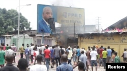 FILE - Congolese opposition supporters chant slogans as they destroy a billboard featuring President Joseph Kabila during a march calliing on Kabila to step down, in Kinshasa, DRC, Sept. 19, 2016.