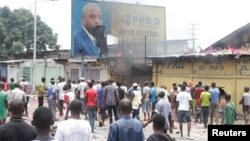 FILE - Congolese opposition supporters chant slogans as they deface a billboard of President Joseph Kabila during a march calling on him to step down at the end of his term, in the Democratic Republic of Congo's capital Kinshasa, Sept. 19, 2016.