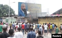 FILE - Congolese opposition supporters chant slogans as they deface a billboard of President Joseph Kabila during a march to press him to step down in the Democratic Republic of Congo's capital Kinshasa, Sept. 19, 2016.