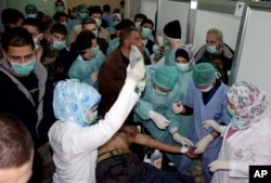 FILE – Doctors treat a Syrian victim who suffered an alleged chemical attack at Khan al-Assal village, March 19, 2013, in this photo released by the Syrian official news agency SANA.