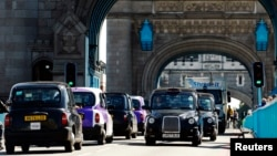 FILE - Traditional black London cabs are seen driving across the British capital's Tower Bridge July 23, 2012.