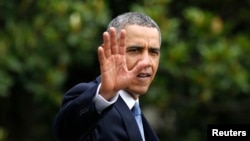 FILE - President Barack Obama waves as he walks towards Marine One on the South Lawn at the White House in Washington.