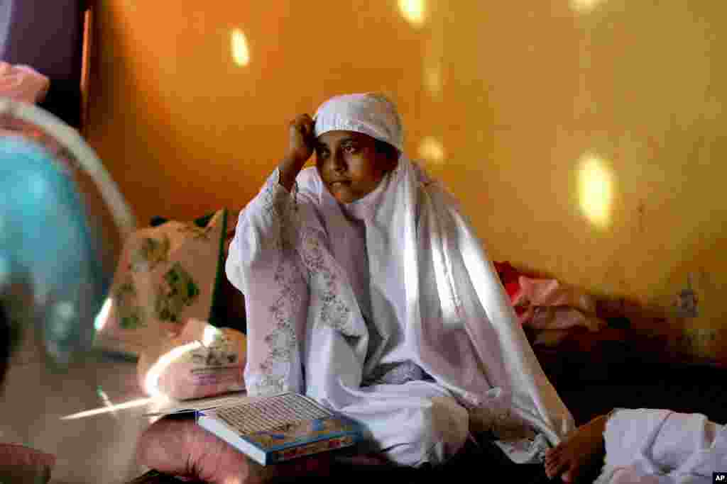 A migrant woman sits after praying at a temporary shelter in Lhoksukon, Aceh province, May 21, 2015.