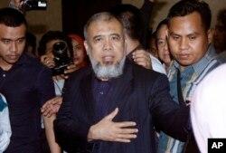 Hakim Mahkamah Konstitusi Patrialis Akbar (tengah) dikawal polisi setelah pembacaan hukuman di pengadilan Tipikor, Jakarta, 4 September 2017.