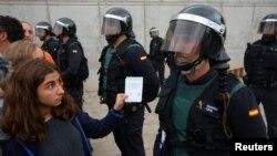 2017年10月1日,在西班牙圣圣胡利娅-德洛里亚市一个被禁独立公投的投票站外,一名女子向西班牙民事卫队人员展示选票。