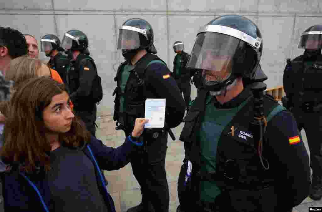 Una mujer muestra una boleta a un oficial de la Guardia Civil española fuera de una mesa de votación para el referéndum de independencia prohibido en Sant Julia de Ramis, el 1 de octubre de 2017.